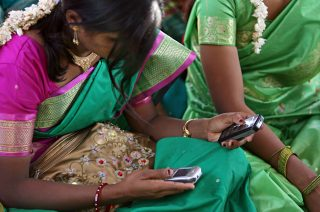 India, 2009: A young woman uses mobile phones during a community meeting in Aurangabad.