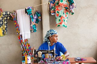 Young woman in traditionally patterned blue headscarf works at an old Singer sewing machine