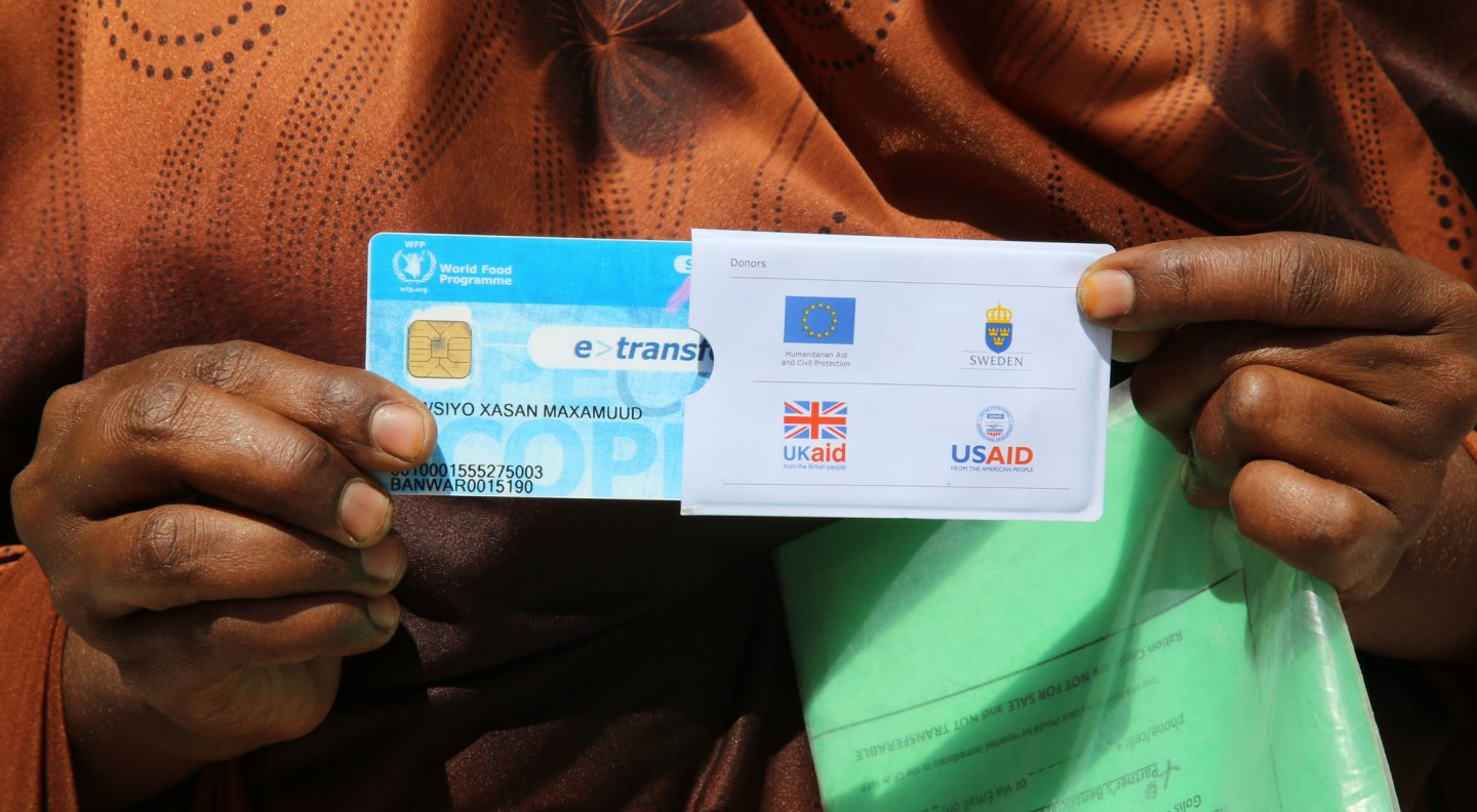 A woman holds a World Food Programme e-card in Somalia, March 2017. The e-cards, which are supported by the UK and other donors, are a secure and cost-effective means of delivering cash transfer programmes to people in need of food. The cards come pre-loaded with a small amount of money so that people can choose to buy which basic items they need from local shops and markets.
