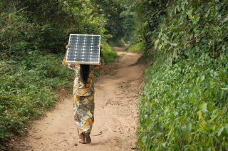 Woman carrying a solar pannel near Yangambi, DRC