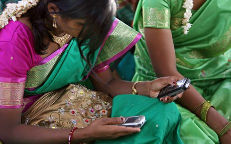 A young woman uses mobile phones during a community meeting in Aurangabad..jpg